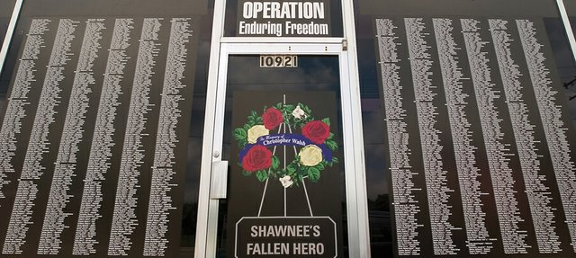 A massive, solemn list of soldiers killed in the Afghanistan and Iraq conflict fills the storefront windows of Prepress Graphic Professionals. A single tribute to Chris Walsh, a Shawnee native killed in action last year, graces the office's central door.
