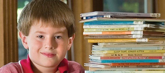 Andrew Moritz, 7 of Shawnee, shows off some of the books he read this summer to get to his goal of 400 books. He started out with a goal of reading 100 books to be like his cousin. Once Moritz reached his first goal, he kept increasing it for a challenge.