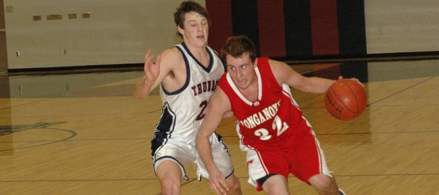 THS junior Jamie Everett dribbles down the left sideline against St. James Saturday in Lenexa. Tonganoxie lost, 49-40.