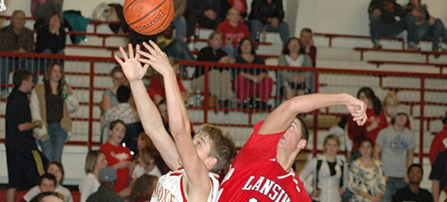 Tonganoxie's Tyson Letourneau, left, and Lansing's Ryan Delich go after a rebound Thursday night during Lansing's 60-37 victory at THS.