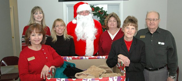 Employees from Reece and Nichols held its inaugural coat drive at their Tonganoxie office from 12 to 3 p.m. Saturday. Back row, from left, are Sandy Waller, Janet Shumway, Santa Claus, Carol Wiley and Jim Edmonds. Front row, from left, are Ruby Rorabacher and Linda Hobbs. The drive received about 65 donated coats. Bottom photo: Annabelle Edmonds, 6, Tonganoxie, sits on Santa Claus' lap on Saturday at the Reece & Nichols office in Tonganoxie. Edmonds and her father, John Edmonds, donated three coats to the First Annual Coat Drive.