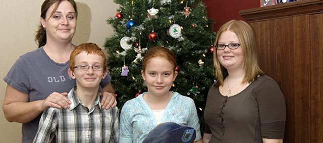 Leanne Peel, left, stands with her three children, who are holding a cardboard cutout of their father, Joe Peel. This is the first Christmas the children won't spend with their father, who is serving as a U.S. Army Specialist in Iraq. The children, from left, are J.D. Peel, Haleigh Peel and Torrie Evans.