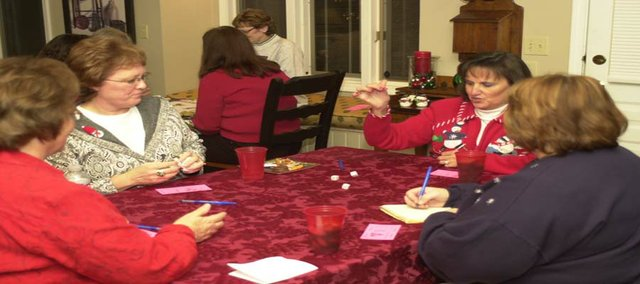 Debbie Maniez rolls the dice Monday at her Bunco club's monthly gathering. The club  donated $700 collected in the last year to charities in the last month.