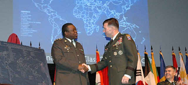 Lt. Col. Colin Mitchell, of Trinidad and Tobago, left, presents Lt. Gen. William B. Caldwell IV, commanding general at Fort Leavenworth, with the class gift during a ceremony Thursday, Dec. 13. The etched glass map was presented during the badge ceremony that gives special recognition to the international students who graduated this year.