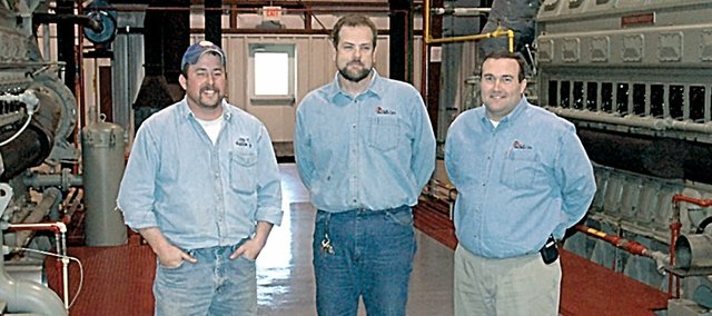 Standing with the city's new power generating engines are city employees, from left, Chris Croucher, lead lineman, Rob Culley, power plant supervisor, and Jeff Dingman, city administrator. Culley kicked the engines into action during the Dec. 1 outage.