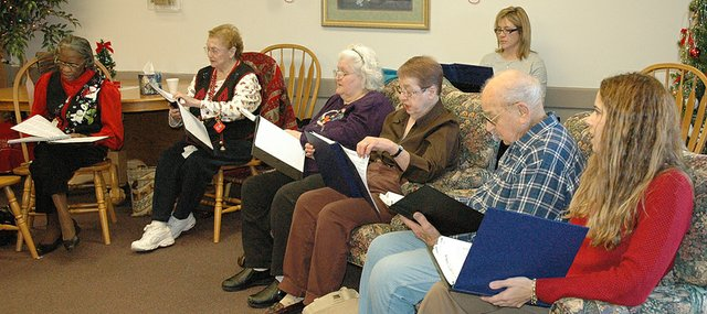 Members of the Council on Aging Sing-A-Long choir perform for the residents of Shawnee Plaza Residence, Leavenworth, on Tuesday, Dec. 18. Singers from left to right are: Viola Hannah, Dorothy Ratliff, Carolyn Crosby, Jean Vance, Richard Cassella, Julie Angello and Victoria Gibson on piano in back.