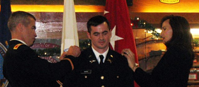 Daniel Roper Sr., left, and Vicki Roper, right, pin new insignia to the uniform of their son, Daniel Roper Jr. The younger Roper was commissioned a second lieutenant in a University of Kansas' Army ROTC ceremony last week. Roper Sr. recently returned from active duty in Iraq to be present for the ceremony.