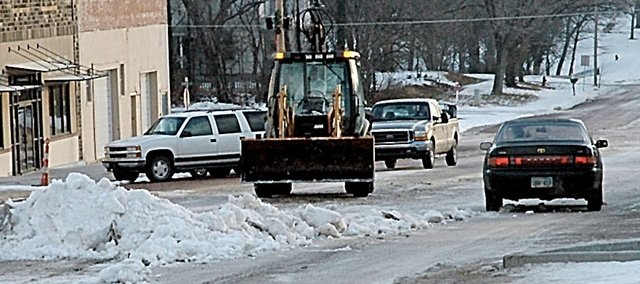Baldwin City's snow removal crew was at it Wednesday morning removing the center snow piles down High Street. Officials say sand and salt supplies are still fine despite the recent winter storms.
