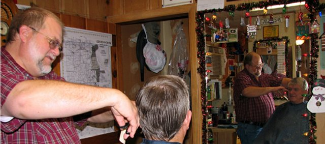 Basehor barber Paul Runnels cuts Piper resident Vearl Jones' hair Friday afternoon at Hair Mechanix. Paul Runnels' father, Dwight Runnels, who died Dec. 10, opened the shop in Basehor more than 40 years ago.
