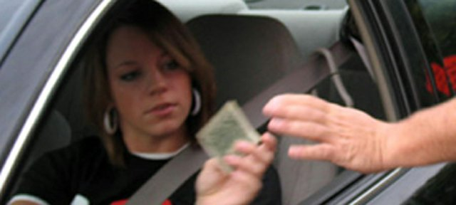 In September 2007, Lansing Police Officer Brian Duncan, right, was handing out dollar bills near Lansing High School to students wearing their seat belts while driving. Now, with enforcement of a new law beginning Jan. 1, Duncan and other police officers may be writing tickets to teens ages 14-17 - drivers and passengers - who aren't buckled up.