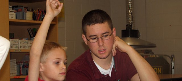 Glenwood Ridge Elementary School second-grader Simon Commerford, left, raises his hand to answer a question under the watchful eye of  Basehor-Linwood High School senior and Care Cat Matt McKinley. McKinley has been mentoring students in Kathy Brown's second-grade class as a YouthFriends Care Cat this year.