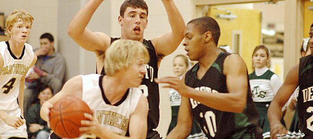 De Soto senior Erik Hill (12) and junior Jamell Townsend swarm a Gardner Edgerton player with defense Tuesday. The Wildcats rallied from a 12-point deficit to take a two-point lead, but the Trailblazers went on to win by six points, 55-49.