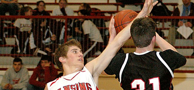 Bobby Hauver, left, obstructs Jefferson County West senior forward Tom Shirley's shot during Lansing High's 48-46 victory Monday in the first round of the Tonganoxie Invitational Tournament.