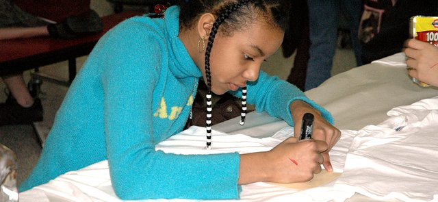 Ariana Clark, 11, draws a star on a T-shirt using a marker and stencil Tuesday during the Lansing Lions Booster Club's annual spirit T-shirt design event. About 118 Lansing Middle School students attended the free after-school event where they were also provided with drinks and snacks.
