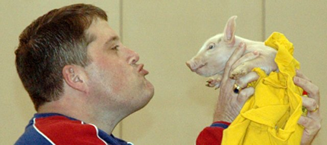 Kerry Brungardt, principal of Lansing Middle School, kisses a pig Friday in front of the entire school population during the final pep rally of the season. Both Brungardt and assistant principal Brooks Jenkins agreed to kiss a pig if the students raised more than 2,000 cans of food during the LMS student council's annual can drive.