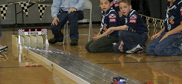 Bear Scouts with Lansing Cub Scout Pack 3165 Den 4 watch as their Pinewood Derby cars race to the finish line Saturday afternoon in the Lansing Middle School gymnasium. Cub Scouts busied themselves crafting their own racecars leading up to Saturday's annual event.