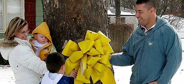 Lt. Col. Pat Cook, right, takes down the yellow ribbon his family hung in his honor during his 15-month deployment to Afghanistan. Cook's wife Wendy, left, his son Casey, 10-months, and son Chase, 8, helped take the ribbon down after returning home Jan. 12. The ribbon hung on a tree in the yard of Cook's in-laws, Carol and Jim Murray, Lansing.