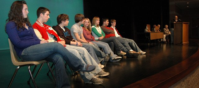 Members of the Tonganoxie High School debate team listen to Mike Yanez during an assembly Wednesday, Jan. 23, recognizing the debate team for its strong showing at state. Pictured, from left, are team members Ann Erickson, Matt Williams, Jon Lane, Dalton Lawson, Addy Phelps, Alicia Osborne, Jake Bontrager and David Powell.