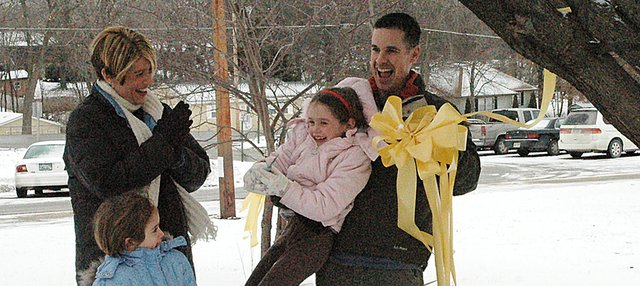 Maj. Seth Weaver holds his daughter Megan, 7, after they cut down a yellow ribbon that hung on a tree outside Lansing Elementary School in honor of her father. Weaver's wife, Patricia, and daughter Mackenzie, 5, look on as the family celebrates Weaver's return from Iraq.