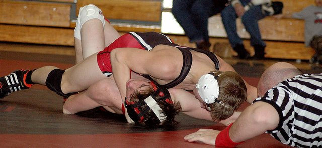 Lansing High senior Dennis Wood puts the finishing touches on a pin of Tonganoxie's Kevin Hamm.