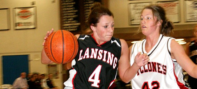 Katie Nietzke, Lansing High senior, drives past a Bishop Ward defender Tuesday night during Lansing's 46-39 victory. Nietzke led LHS with 14 points.