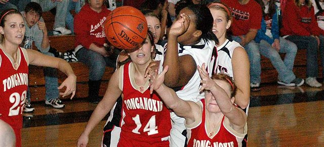 Lansing junior Alexis Ellis reaches over Tonganoxie senior Tracie Hileman during a battle for a rebound Friday night.