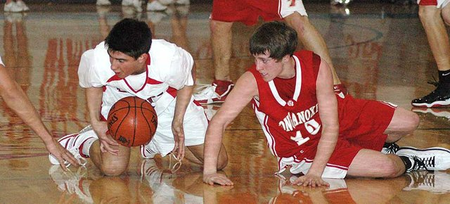 Lansing junior Curtis Beall and Tonganoxie junior Jace Waters battle for control of a loose ball during Lansing's 49-43 victory Friday night.