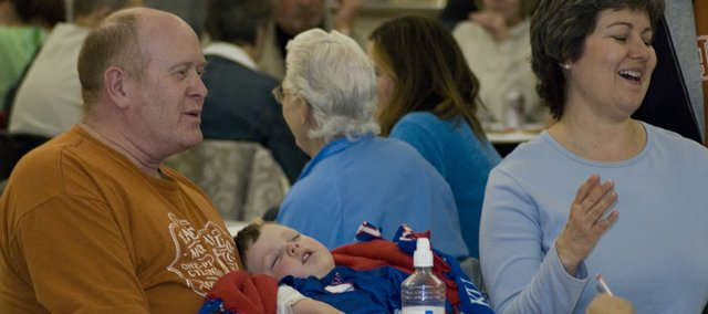 Exhausted from celebrating his 3rd birthday, Cole Parker sleeps through all of the commotion of Saturday's fundraiser in Herb George's arms while he and his wife, Tammie George, Tonganoxie Elementary School principal, play bingo. The fundraiser was a part of the Tonganoxie High School's Project Graduation, which is raising money for an after-graduation party for THS seniors.