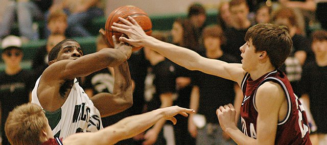 De Soto's Andre Linzy has his shot blocked Tuesday as the Wildcats battled Eudora. Linzy and the Cats bounced back from the momentary setback, beating the Cardinals for the second time this season.