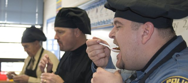 Erik Lynnes, foreground, from the Basehor Police Department, takes a bite of chili during the judging portion of Thursday's Chilingo event at Basehor Elementary School. As official Chilingo judges, Lynnes, Superintendent Robert Albers, left, and Assistant Superintendent David Howard, center, sampled chili from 27 different classes and decided that Diana Manford's fifth-grade class made this year's best chili.