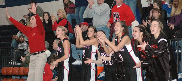 Lansing High coach Keith Andrews, left, calls out the defense while LHS players Amanda Darrow, Morgan Chiles, Katelyn Griffen, Retha Cioppa, Katie Cristiano and Kari Kelly cheer after Alexis Ellis sank two free throws that put the Lions ahead for good in their 67-60 victory over Mill Valley.