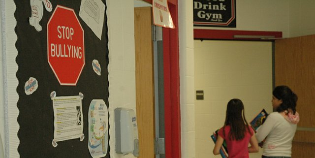"Students of Lansing Middle School walk by a poster during their passing period advocating them to ""Stop Bullying."" The poster is one of many programs LMS is doing to cut down on bullying as an effort to make students feel like school is a safe environment where they can learn."