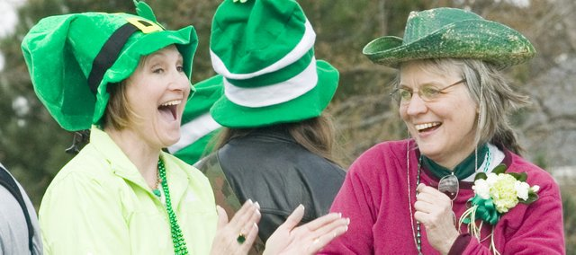Debbie Breuer, left, and Kay Soetaert, ride on the back of the County Road 5 Band's float. Breuer and Soetaert helped organize the St. Patrick's Day Parade.
