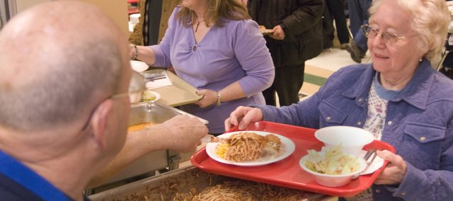 Mel Ramseier, left, scoops spaghetti onto Betty Lingenfelser's plate during Friday's fish fry.