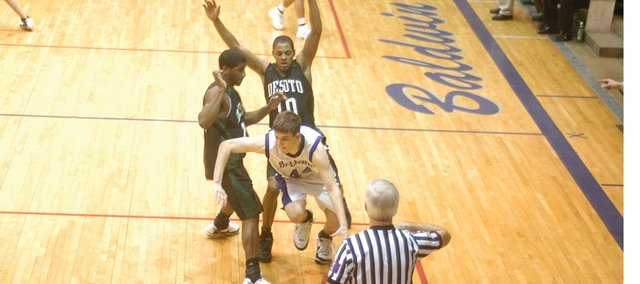 De Soto basketball players Andre Linzy and Jamell Townsend trap a Baldwin opponent. The Wildcats lost, 59-58.