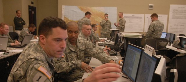 Maj. Gary Belcher, left, answers a simulated call from the field as part of a computerized training exercise at Fort Leavenworth's Command and General Staff College and Combined Arms Center. More than 60 American and foreign military officers studying at the fort took part in the war game called a digital warfighter exercise.