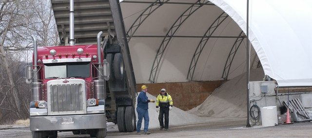 "Trucker Rob Williams (left) and city of De Soto Street Department employee Gene Russell finish dumping a load of salt Tuesday at the salt storage ""dome"" on Ottawa Street. The city contracted with Betty Cannon Trucking to deliver 75 tons of salt from Hutchinson to replenish a supply nearly exhausted from the season's many storms."