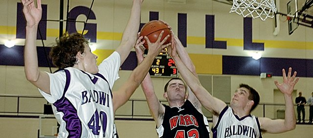 It was a battle for the rebounds Friday night in Spring Hill during the Class 4A sub-state semifinal game. Here Baldwin High School freshman Justin Vander Tuig, left, and senior Drew Berg (No. 44) compete against Bishop Ward's James Cox (No. 43) for a rebound. Bishop Ward won the game 47-45 on a last-second three-pointer by Cox.