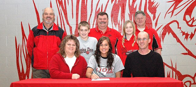 Morgan Chiles, center in front row, will play softball at Johnson County Community College. Seated with her are her parents, Mike and Lisa Chiles. Also pictured are, middle row, from left: siblings Camden Chiles and Sydney Chiles and, back row, LHS coach Terry Cornett and Leavenworth Twisters coaches Dave Clevengre and Rick Cook.