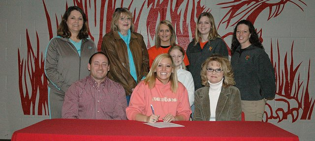 Kristen Jensen, center in front row, signs her letter-of-intent to play volleyball at Neosho County Community College. Jensen was joined at the signing ceremony by her family, LHS coach Julie Slater, back left, and Neosho assistant coach Kaylee Niday, second from right in back row, and NCCC head coach Lindsay Sowder, far right in back row.