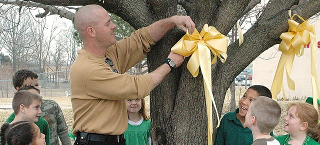 Sgt. Daniel Johnson, left, cuts down a yellow ribbon that was hung for him by his son Daniel Johnson, 8, right. Johnson was deployed for Afghanistan in November 2006 and returned home Thursday, March 13.