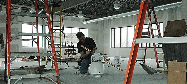 A member of the construction crew works in the new Lansing location of Anytime Fitness at the corner of Kansas Avenue and Main Street. The gym will open in the coming weeks and members are currently being accepted.
