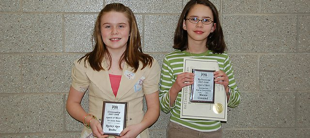 "Hailey Budke, left, and Maisie Conrad, right, pose with the awards they received during the Kansas PTA Awards ceremony held Saturday, March 8. A total of four Lansing students were recognized. ""Awards of merit"" for winning the regional competition and then going on to receive honorable mentions in the state competition were given in the Reflections fine arts program,: Conrad, 10, for music; Caitlin Starman, 9, for photography; and Meg Szmed, 10, for visual arts. Budke was given an award for being the statewide winner of the ""Citizenship"" essay contest, which asked students to write an essay about how to improve the existing government. Budke wrote her essay on the use of alternative fossil fuels."