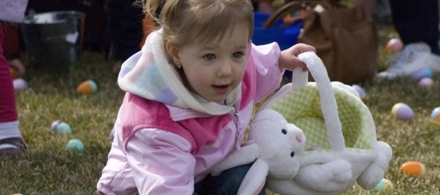 Two-year-old Alyssa Novotney bends down to pick up Easter eggs during Saturday's egg hunt at Chieftain Park. About 500 people attended the annual egg hunt sponsored by the Tonganoxie Recreation Commission.