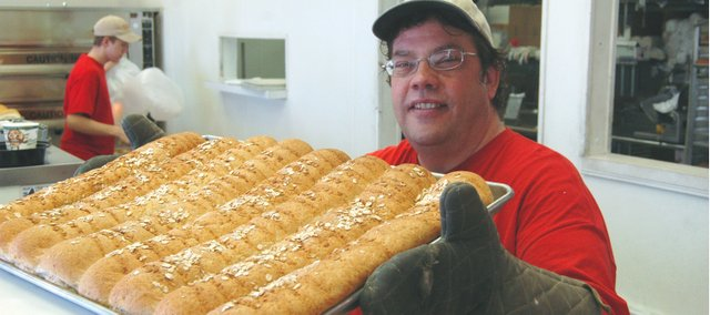 Mr. Goodcents owner Mark Matheson takes a pan of bread out of the oven at his Tonganoxie restaurant. The eatery is celebrating 10 years of business in Tonganoxie.