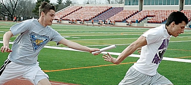 Baldwin High School juniors Connor Wright, left, and Sam Beecher work on baton exchanges Tuesday afternoon for the 400-meter relay in preparation for Friday's home meet.