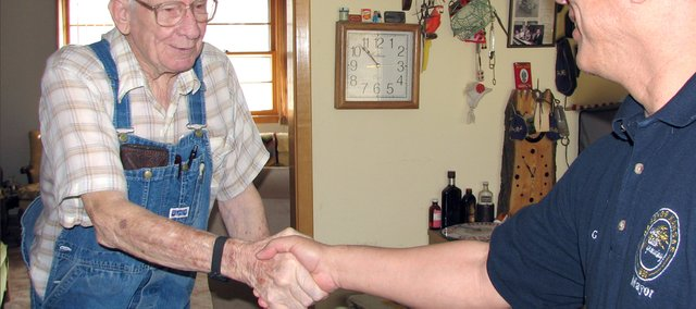 Basehor Mayor Chris Garcia (right)  shakes the hand of Basehor resident Marion McBrien after bringing him lunch in his home Wednesday morning. Garcia delivered Meals on Wheels to a few seniors in the community as a part of the national Mayors for Meals and March for Meals campaign through the Leavenworth County Council on Aging.