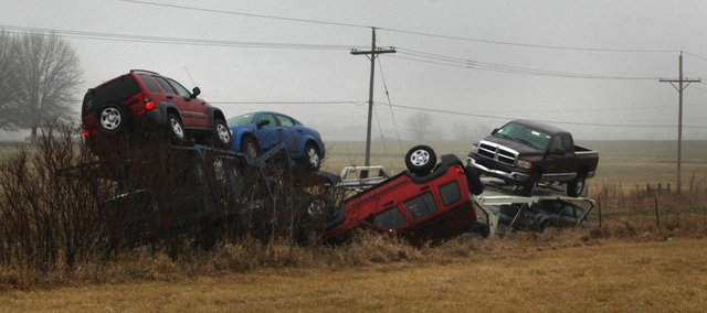 A car hauler, as well as several vehicles it was hauling, rests Thursday in the ditch west of U.S. Highway 24-40 near Kansas Avenue. According to the driver of the vehicle, the interior and exterior lights on the hauler went out as he was driving about 9 p.m. Wednesday and his vehicle went off the road where the highway curves.