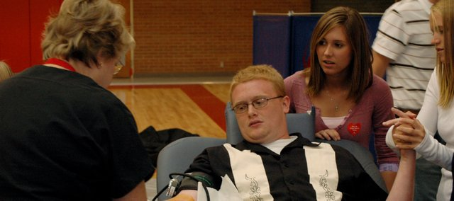 In 2006, then Tonganoxie High School senior Henry Johnson receives moral support from Christy Weller, right, as Debbie Jones from the Community Blood Center draws blood from him during a blood drive in the THS gymnasium. The THS Student Council sponsored the drive, which generated more than 90 units of blood. The student council will have another blood drive in the spring.