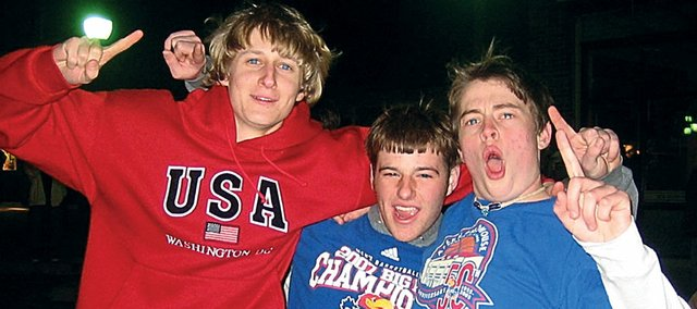 Three Baldwin High School seniors celebrate Monday night on Massachusetts Street in downtown Lawrence after the University of Kansas won the NCAA mens' basketball championship. Pictured here, from left, are Dan Glover, Brock Robertson and David Lynch. Several other BHS students joined thousands of fans Monday night to celebrate KU's first title since 1988.